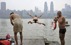 Un hombre salta en el río Yangtze junto a otros nadadores  en el municipio de Chongqing.
