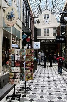 The Ultimate Parisian Guide To Paris: Passage Jouffroy | Hidden in the 9th arrondissement, this is one of Paris' many small passages, equipped with a gorgeous glass ceiling and lined with very quaint antique shops, bookstores, and candy stores. It can get touristy because of the wax museum next door, but it remains a prime location for artsy Instagram pictures. Try having brunch upstairs at Le Valentin — you can watch the entire gallery from the sumptuous couches.