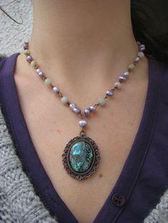 Krása řeky Náhrdelník se skládá z říčních perel v jemně fialovém odstínu a kuliček amazonitu. Komponenty v měděnébarvě, přívěsek z ozdobného lůžka a kabošonu z mušle paua.