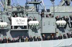 """An Ensign, Megan M. Hallinan, (my roomie)serving about USS Winston S. Churchill, wrote a letter to her father in with the accompanying photo taken by 2nd class Shane McCoy  the days immediately following 9/11.  The photo shows the entire crew of German sailors aboard the German destroyer FGS Lutjens manning the rails in their dress blues.  They were flying an American flag at half-mast while holding up a banner reading """"We Stand By You""""."""