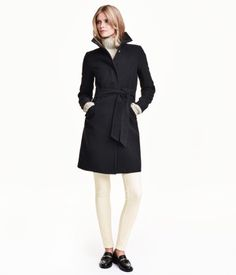 Gently flared coat in felted fabric with a stand-up collar. Concealed snap fasteners at front, side pockets with decorative flaps, tie belt at waist, and vent at back. Lined.