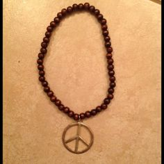 Just REDUCED!! Wooden Beads PEACE Necklace This lightly tarnished gold metal peace sign hangs from a brown wooden beaded necklace. Cool effect! Worn choker style. Jewelry Necklaces