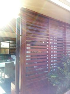 Outdoor patio area with an extended wooden slatted roof, side wall and deck.