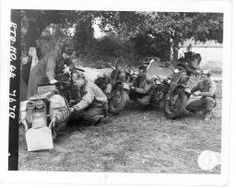 """Messengers caring for their """"bikes"""" while they have a chance. L to R : Pvt Lambert J Keeler, Chicago, Ill., Pvt Robert Wise, Eugene, Ore., Pvt Orval W Foster, Wells, Kansas, and Pvt Charles Haugland, St Louis, Mo., working on their motorcycles. 2 armd div., Carentan, France. 15 july 44 = [Quatre messagers de l'armée américaine examinent leur moto]. http://recherche.archives.manche.fr/?id=recherche_documents_figures"""