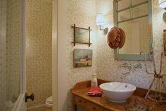 Une ancienne fenêtre devient le miroir au- dessus du meuble-lavabo, lui-même étant un meuble ancien recyclé pour cet usage. L'endroit a un charme vieillot et charmant.   (alison_kandler_8.jpg)