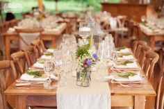 Farm style wooden dinner tables set with rough linen runners and local wildflowers in simple glass vases... sprigs of herbs like rosemary and mint adorned dinner plates to create a warm and earthy feel for this tented wedding reception in Stowe, VT.