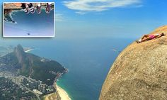 Daredevils hang over edge of a 2,769ft cliff-face for the perfect shot