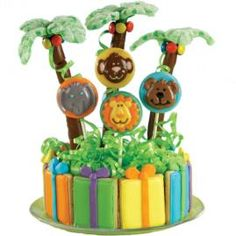 Happy Habitat Cookies & Candy. This fanciful tableau is a party in the making. Surround a foam base with cookies wrapped in color flow icing. Add Animals Cookie Candy Mold lollipops and palm trees.