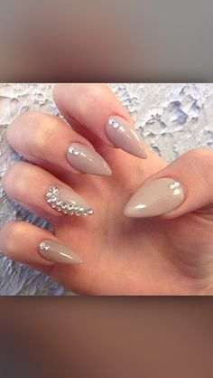 Rhinestones on nude, stiletto nails.