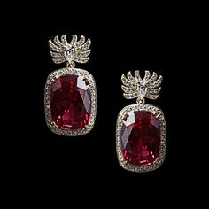 These stunning drop earrings showcase a cushion cut ruby stone with clear pave set cubic zirconia accents set in sterling silver with vermeil plating.