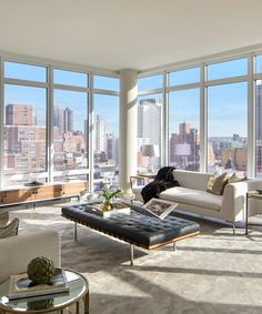 This home features exquisite floor-to-ceiling windows offering breathtaking views of the East River—take a look around! Pictured above, living room.