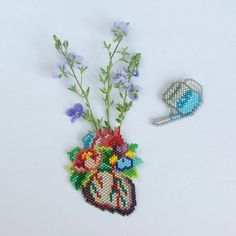 Hand beaded blooming heart with a watering can are available as brooches or a heart pendant on a gunmetal chain. The very tiny glass beads are carefully