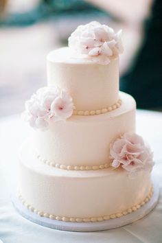 Three tier white wedding cake with blush pink flowers. Photography: Three Nails Photography -
