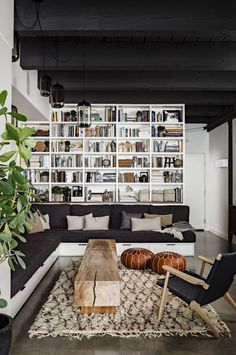 What a cool living room! The black ceiling is awesome and really makes the home library pop & be the center of attention. Plus, there's great lighting and decor as well!