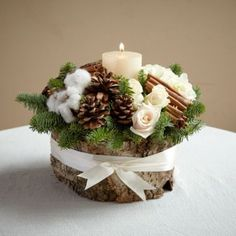 a wooden log with pinecones, evergreens, cinnamon sticks and a candle