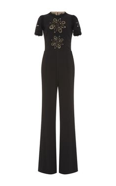 This short sleeve **Elie Saab** jumpsuit is rendered in crepe cady and features a rounded neckline with macramé embroidery along the bodice and a flared pant.