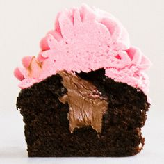 Nutella Stuffed Chocolate Raspberry Cupcakes feature a perfect chocolate cupcake stuffed with Nutella and topped with a delightful raspberry buttercream.