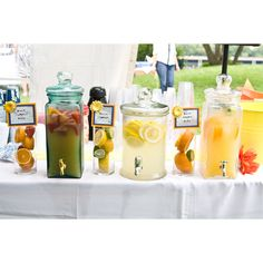 A fun assortment of summer drinks in a variety of drink dispensers.