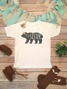 Big Sister T-Shirt (or bodysuit)  Boho baby boy bodysuit (or shirt) with big sister printed across the front inside a bear silhouette with cute floral headdress/wreath. Perfect for your oldest little bear cub. Also makes a great gift or pregnancy announcement. Pair it with our other bear family shirts for an adorable Big Sister Little Sister (or brother) Shirt set. **This listing is for one item only, the big sister bear silhouette bodysuit or shirt in your choice of brand and size. >...