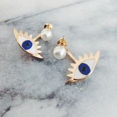 Our evil eye ear jacket earring is equal parts quirky and ladylike - a single pearl balanced atop an enamel eye, complete with flirty gold
