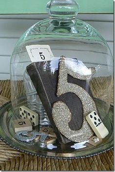 This is gorgeous table number centre piece, collect items with your table number and display them under a bell jar.  A centre piece and table number all in one, if you placed it on a mirror and surrounding it with flowers or tealights, then you are pretty much done in terms of your central table decoration.