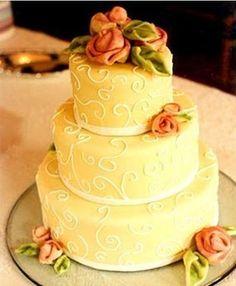 Torta nuziale raffinata color crema con rose