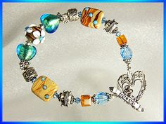 This exquisite, one of a kind handmade crystal bracelet has it all – aqua-blue Murano glass hearts, earth toned lampwork beads, Swarovski crystals and sterling silver Bali beads.  Isn't it adorable?