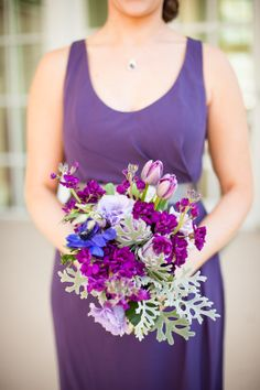 bridesmaids bouquet of purple anemones, lavendar roses, purple tulips, purple lisianthus, purple stock and dusty miller.