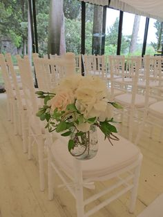 Glass jar for the chairs with white hydrangea, white lisianthus and ivory roses. Event Planner : Wedding Italy.