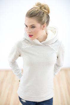 Wunderbar kuscheliger Hoodie aus beigem Sweatshirtstoff. Eine creme farbene Spitze ziert die Schultern.