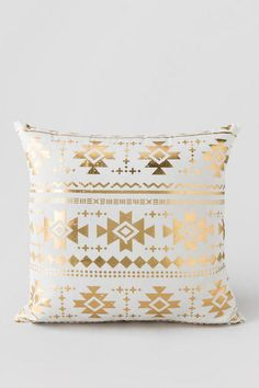 "Refresh your home or apartment with the beautiful Gold Aztec Pillow! A shiny gold, tribal inspired design is printed on the front of the pillow for a bold yet feminine touch. Pair with our additional home & decor options to complete your room.<br /> <br /> - 20"" x 20""<br /> - Cotton cover<br /> - Polyester fill<br /> - Made in the USA<br />"