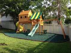 Fantasy Tree House swing set with spiral tube slide and rubber mulch surfacing.