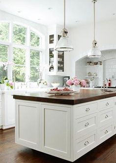 Breathtaking white kitchen with butcher block island. Love the windows!