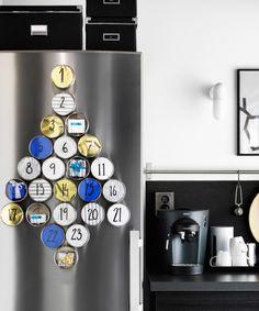 Ein Kühlschrank mit Edelstahlfront, auf dem magnetische GRUNDTAL Behälter aus Edelstahl zu einem Weihnachtsbaum angeordnet, mit Nummern versehen und kleinen Geschenken gefüllt sind.