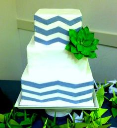 Three tier square white wedding cake with blue horizantal lines and green flower