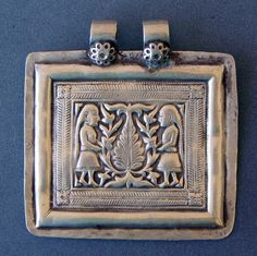 Silver Amulet   Himachal Pradesh, North India ~                                       In the middle the Tree of Life (axis mundi), which connects the three worlds  (underworld, world of men, world of the gods)  Right and left a women, each one is holding a part of the tree.  A rare piece, probably 19th century