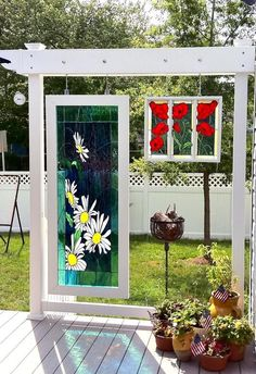 Stained glass windows displayed on garden arbors by a deck. Very pretty!