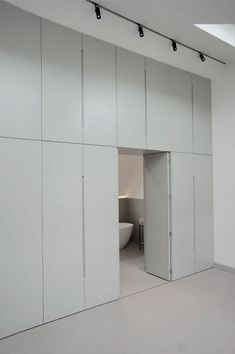 A loft extension in Brixton by studioort. The key design element providing the spatial organisation of the loft is a floor to ceiling wardrobe/storage wall. The divider creates a 'hidden' en-suite whi Wardrobe Wall, Wardrobe Design Bedroom, Wardrobe Storage, Built In Wardrobe, Closet Bedroom, Diy Bedroom, Closet Wall, Trendy Bedroom, Closet Doors