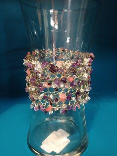 Glass vase with a decorative wire crochet collar. Amethyst, Clear and Rose Quartz.