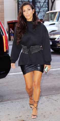 Kim Kardashian gave her oversize men's sweatshirt a sexy spin by belting it with a waist-cinching corset, adding a leather mini, and stepping into delicate lace-up sandals.