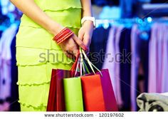Image of shopaholic hands with three shopping bags by Pressmaster, via ShutterStock