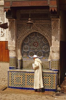 Fez, Morocco - A Man Stops for a Drink at the Nejjarine Fountain in the Old City of Fez.