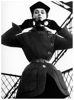 Dovima wearing a fleeced, belted tunic by Dior at the Eiffel Tower, Paris, August 1950. Photo by Richard Avedon.