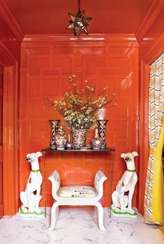 I LOVE the fretwork paneling on the wall. And the high gloss orange paint makes it all seem so glamorous. I could live without the dogs.