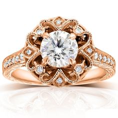 A round-cut moissanite gemstone grances the center of this stunning vintage-style engagement ring, crafted of 14-karat gold in your choice of color. The setting is studded by genuine, round-cut diamonds.
