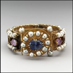 Jeweled Bracelet (one of pair) Date: 6th–7th century Geography: Made in probably Constantinople Culture: Byzantine Medium: Gold, silver, pearls, amethyst, sapphire, glass, quartz Dimensions: Overall: 1 1/2 x 3 1/4 in. (3.8 x 8.2 cm) strap: 7/8 x 7 11/16 in. (2.3 x 19.5 cm) bezel: 1 5/16 in. (3.4 cm) The Metropolitan Museum of Art