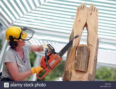 Download this stock image: A womanm treats a trunk with a chainsaw to make art in Extertal, Germany, 28 May 2010. Women are trained in the so-called 'Carving'technique to form sculptures from wood. Photo:Oliver Krato - D58YYW from Alamy's library of millions of high resolution stock photos, illustrations and vectors.