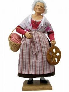 La femme à la fougasse, une Bastidane habillée d'un costume XIXème, de situation aisée et très élégante, elle apporte, en offrandre, un panier de provisions et une fougasse à base d'huile d'olive faisant partie des 13 desserts.