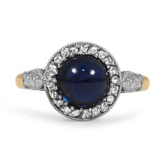 The Wenopa Ring - a round, deep blue sapphire cabochon set regally at its center, encircled by a sparkling halo of accent diamonds and milgrain detailing
