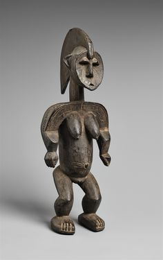AN IGALA FIGURE  Probably by Umale Oganegi, Ukuaja, northern Nigeria  The standing female with tall median-crested coiffure falling down the nape of the neck, flat face with features in relief, prominent breasts, incised scarification to the face and body, black patina.  37 cm. high